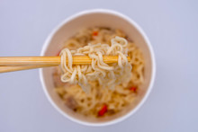 Top View And Close Up: Hot Instant Noodle In The Wooden Chopsticks On White Background. Spicy Taste, Street Food. (selective Focus)