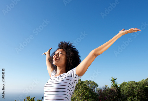 Photo  young african woman standing outdoors with arms raised and laughing
