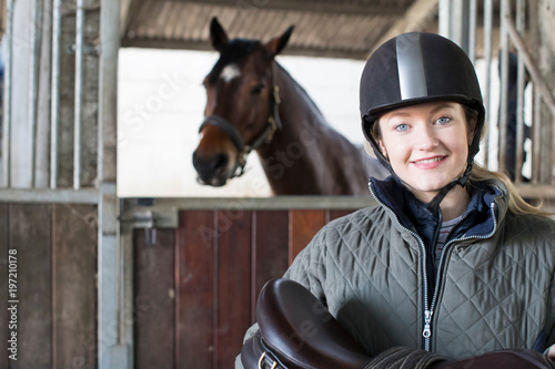 Fotografía  Portrait Of Female Owner Holding Saddle In Stable With Horse