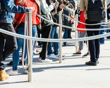 People Standing In Line Between Stainless Steel Queue Poles With Grey Ropes, At The Entrance Of A Tourist Site, Leaning On The Poles Or Watching Their Smartphones.