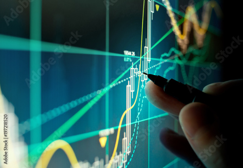 A stock trader checking technical markers of a stock on a computer screen.