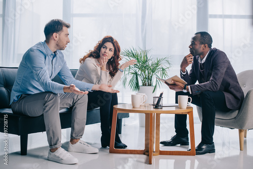 Fotografía  Quarreling couple talking to african american psychiatrist in office