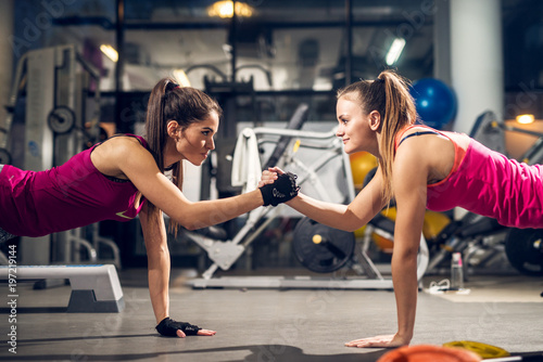 Photo sur Toile Fitness Two young motivated aggressive attractive focused sporty active girls doing push ups and holding hands together while looking each other in the modern gym.