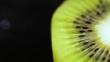 the kiwi lies on a black background. Macro shooting of a kiwi. A kiwi close up on a black background. Juicy green a kiwi