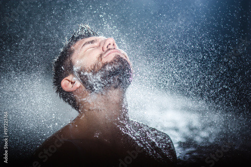 Fotografie, Obraz  Headshot of a handsome fashionable young man taking shower, with water splashes