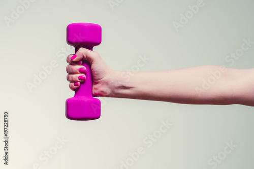female lifting magenta colored dumbbell against teal background Fototapeta