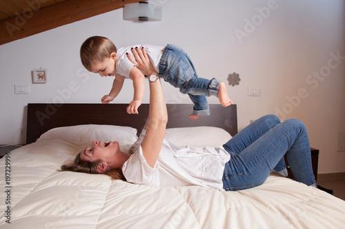 mamma e figlio giocano sul letto Poster