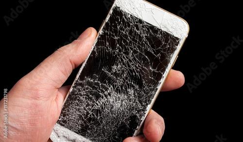 Modern smartphone with highly broken screen in men hand on black background.