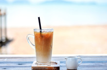 Iced Cold Coffee Glass At The Beach Bar With Blurred Seascape In The Background And Sweet Syrup Jug.
