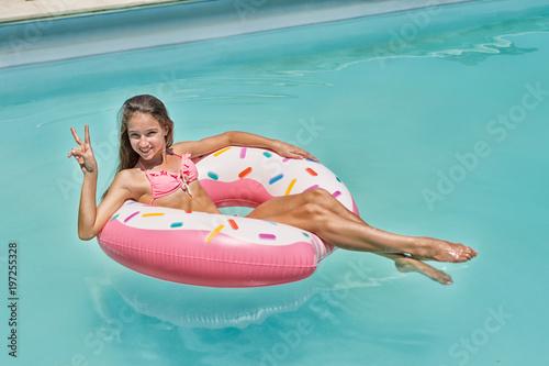 Obraz Teenage girl have fun on inflatable donut in blue swimming pool - fototapety do salonu