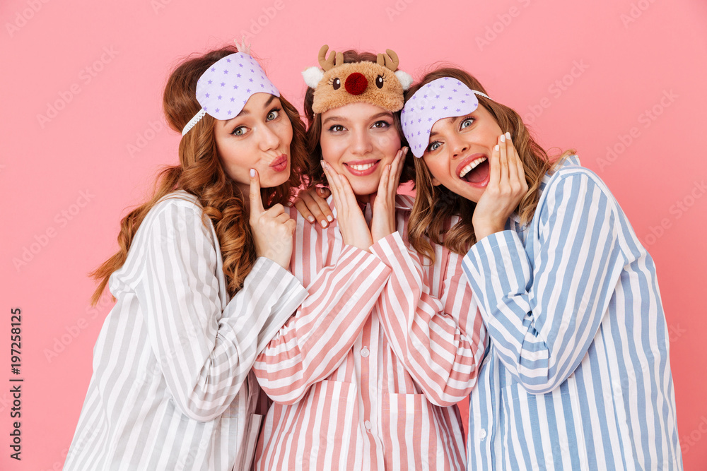 Fototapety, obrazy: Three beautiful young girls 20s wearing colorful striped pyjamas and sleeping masks having fun during girlish sleepover, isolated over pink background