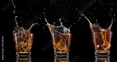 Valokuva set of whiskey shots with splash isolated on black background
