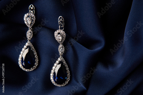 Fotografia Pair of platinum earring with sapphire on blue satin background