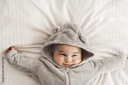 Portrait of a baby boy on the bed in bedroom Canvas Print