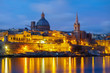 Night view of Valletta, capital of Malta. Beautiful spires and St. Pauls Cathedral and Charmelite Church skyline under blue night sky, lights reflected in the sea bay.