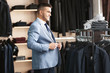 Young man trying on elegant suit in boutique