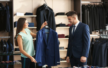 Female Shop Assistant Helping Man To Choose Suit In Store