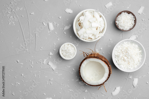 Bowls with coconut flakes on gray background, top view