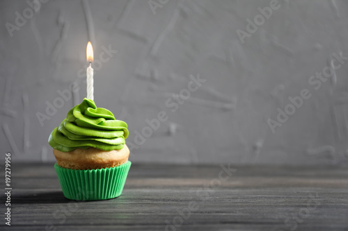Photo  Delicious birthday cupcake with burning candle on table
