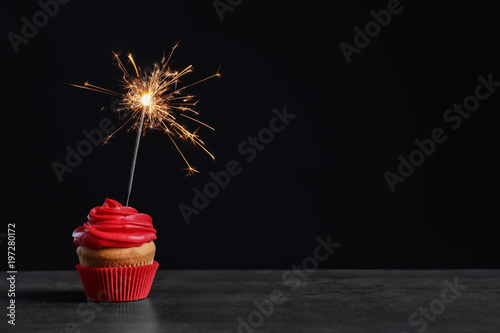 Delicious birthday cupcake with sparkler on table against black background