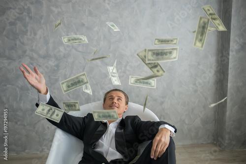 Fototapeta Rich businessman lying in bathtub filled with dollar banknotes. Success business concept. obraz