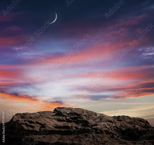 Light from sky . Religion background . Red sunset and moon . Against the background of clouds . beautiful sky . Yellow and pink clouds . Sunset and new moon . Prayer time . Generous Ramadan