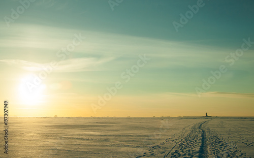 Valokuva  Epic winter landscape with blue tones, deserted surface of frozen sea covered by snow, sunset sky with cirrus clouds and lonely path outgoing to lighthouse