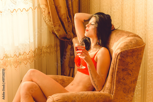 632588e78b1 Attractive lady with thin figure posing at home interior. Lady wearing  sensual lingerie. Seductive sexy brunette women