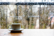 A White Espresso Cup With A Spoon On A Wooden Table In Front Of A Glass Window Covered With Rain Drops.