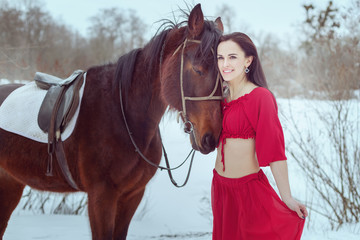 Brunette woman stands in winter forest near horse.