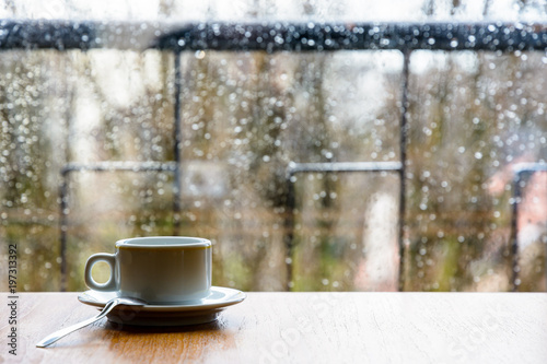 Photo A white espresso cup with a spoon on a wooden table in front of a glass window covered with rain drops