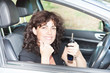 Pretty smiling beautiful woman holding keys while driving a car
