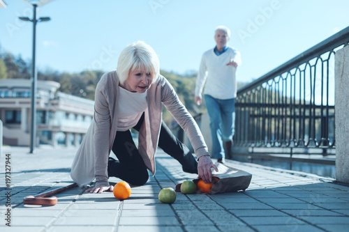 Obraz Are you ok. Selective focus on a scared senior lady standing on her knee and trying to pick up her groceries after falling down while her worried husband running to her in the background. - fototapety do salonu