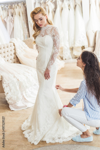 Photo Female tailor working by attractive bride in wedding atelier