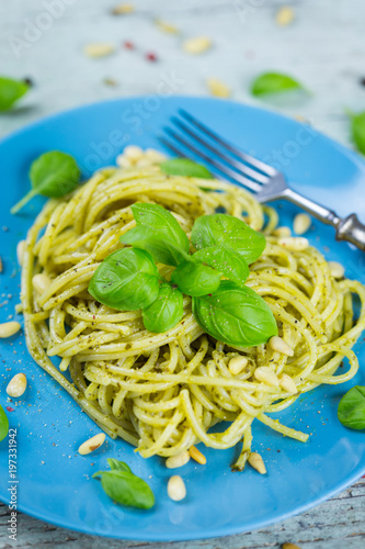 Fotografía  Plate of cooked spaghetti pasta with pine nuts and fresh basil pesto leaves for