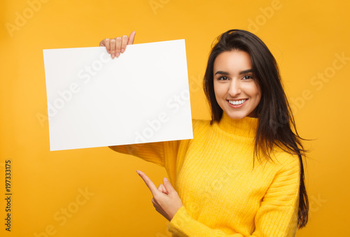 Fotomural  Charming brunette pointing at blank paper