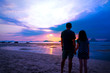 Silhouette of Asian father and teenage daughter holding hands standing together on sunset beach. Daddy and his child girl hand in hand. Fathers day concept, Tub Kaek beach, Krabi, Thailand. Copy space