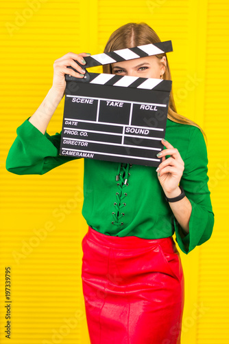 Canvas Print Attractive woman with a clapperboard in her arms