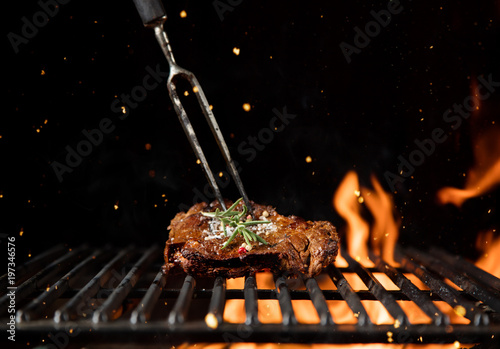 Aluminium Prints Grill / Barbecue Fiery grill grid with piece of beef steak.