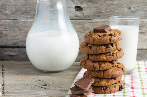 In de dag Koekjes Oatmeal chocolate chip cookies, jug and glass of milk, rustic wooden background.