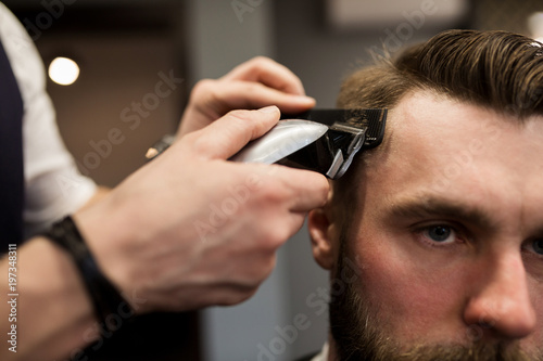 Young man having hair shaved at hairdresser salon