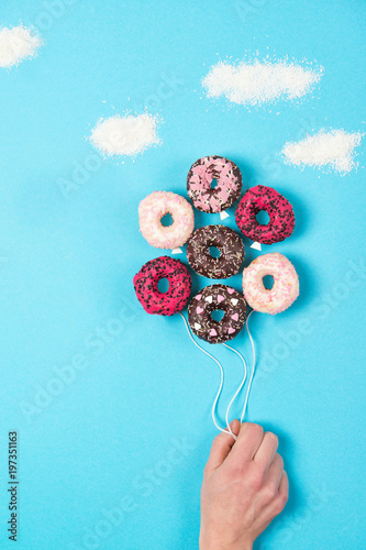 Colored mini donuts on blue background, creative food idea, hand holding donuts in a shape of balloons in the sky with clouds made of coconut, top view