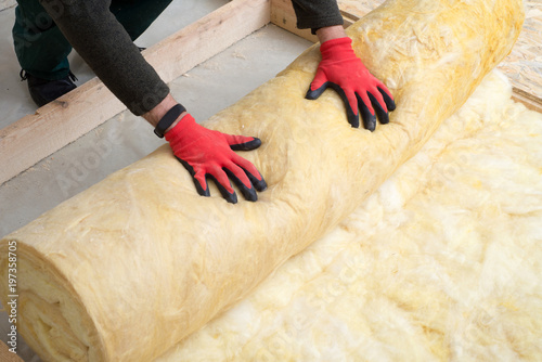Obraz Work composed of mineral wool insulation in the floor, floor heating insulation , warm house, eco-friendly insulation, a builder at work - fototapety do salonu
