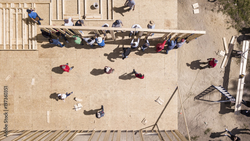 Fotografie, Obraz  Top down view of workers raising a wall on construction of a new home
