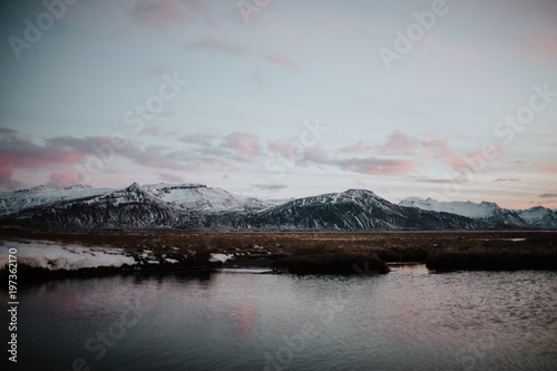 Foto op Aluminium Koraal A lake in Iceland at sunset with some mountains in the background
