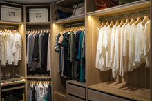 Luxury Walk In Closet / Dressing Room With Lighting And Jewel Display. Dresses, Handbags, Blouses And Sweaters On Hangers In The Wardrobes. Horizontal.
