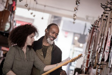Small Business Owner Helping Customer In A Guitar Store