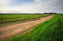 Rural Environment With Wooden Fence Beside The Road. Spring Landscape