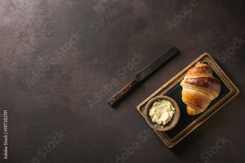 Fresh baked traditional croissant on wooden slate serving board with butter and vintage knife over dark brown texture background. Top view, copy space