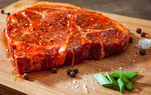 Raw Marinated Meat Steak For Bbq, Pork Chop On A Wooden Chopping Board